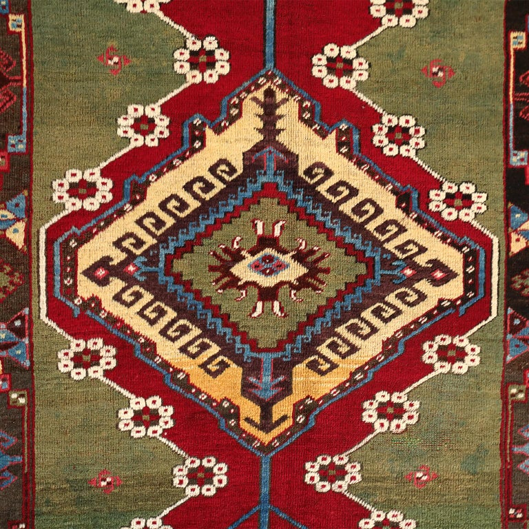 This Turkish Kirsehir carpet circa 1920 in pure handspun wool and vegetable dyes features a hand knotted pile and contrasting coloration, showcasing a geometric central medallion amid fields of red and green. Outlines of light cream, yellow, and