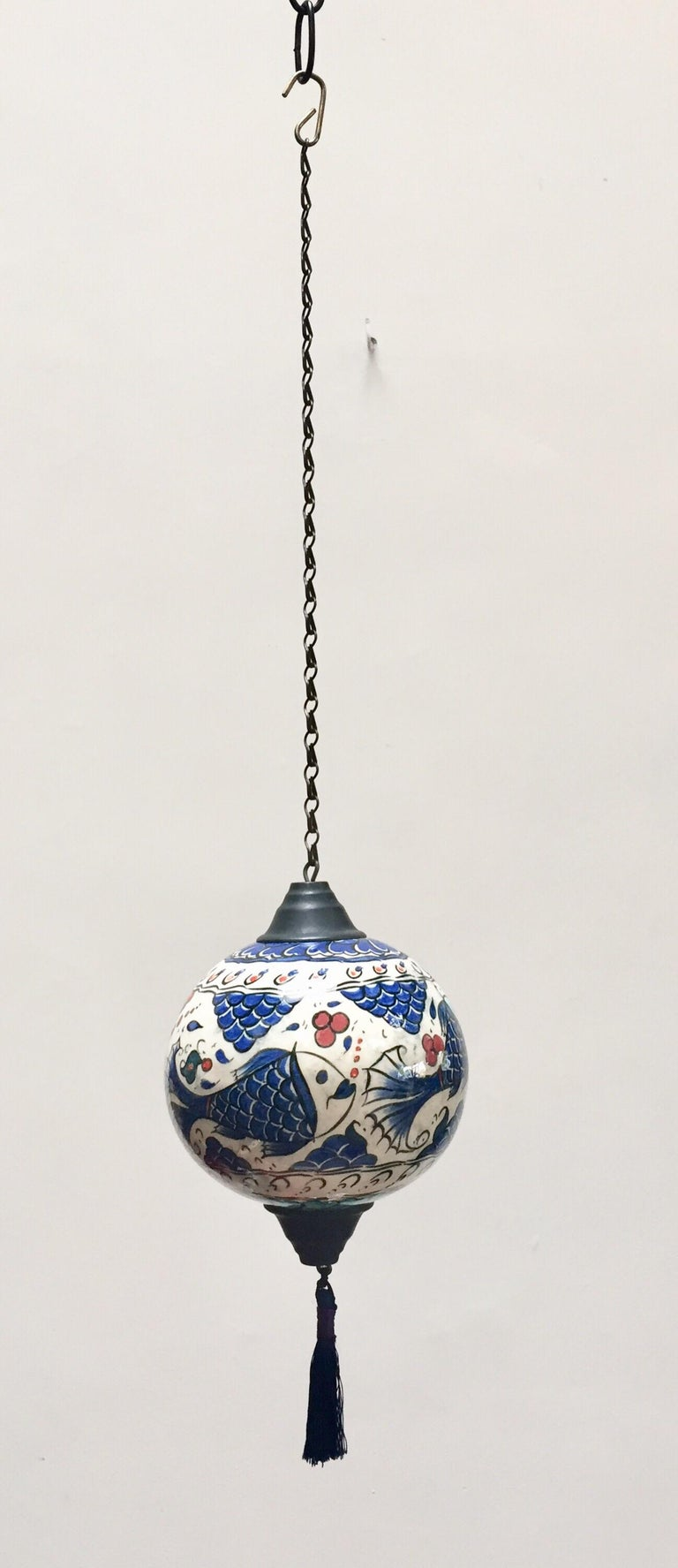 Kütahya pottery hanging ornaments in a bulbous form decorated with fishes underglaze in cobalt blue, turquoise and red on white background. Cobalt blue silk tassel, hang from a black painted chain. A Kütahya pottery hanging ornament in polychrome