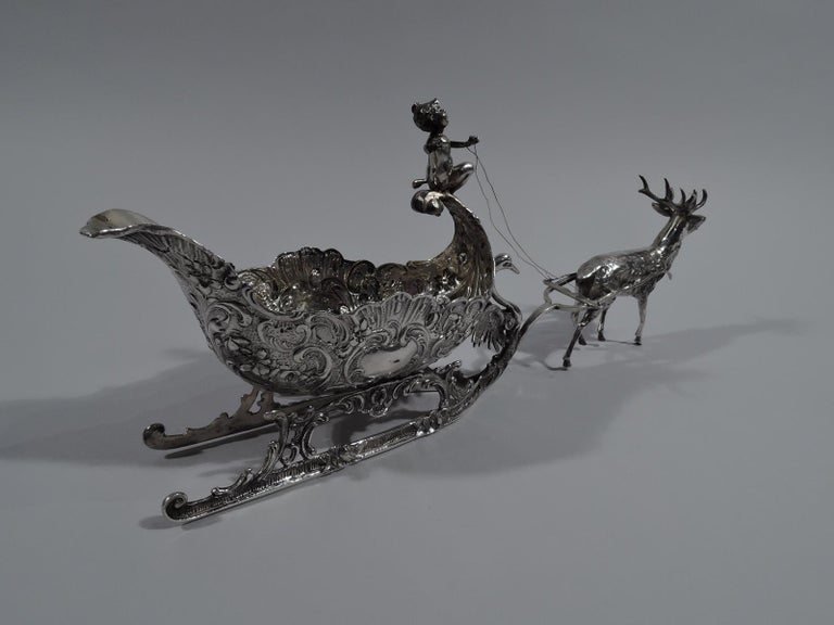 Turn-of-the-century German Rococo Revival 800 silver sleigh. Shaped oval with scrolled rim and chased scrolls and flying scroll front on which is casually perched a drapery-clad cherub holding the reins to a prancing reindeer. Ornamented runners
