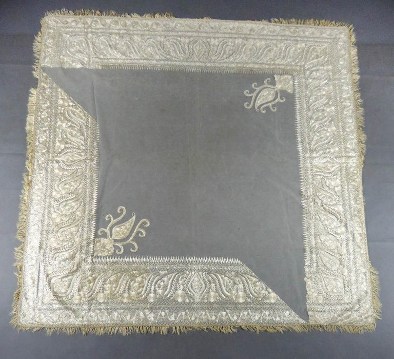 Circa 1840 India for fashion in Europe  Square turn-over shawl in cotton tulle embroidered in Delhi in the mid-nineteenth century and exported for fashion in Europe. Background in very fine cream cotton tulle embroidered with silver cream floss-silk