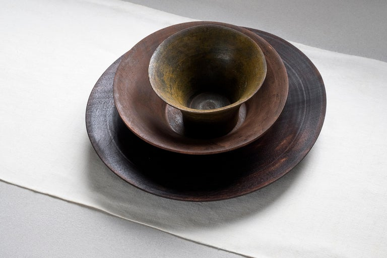 Coral is a set of irregular plate and bowls, masterfully turned with thin thicknesses. The three pieces are made of walnut wood, colored by finishes starting from metal oxides, that twist the material's perception of the object. This table set is