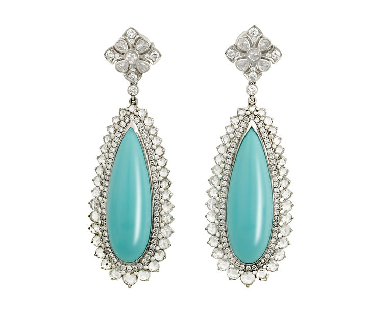 The cool blue of turquoise is accented by the drama of sparkling diamonds in these classic Tiffany & Co. earrings. The turquoise stones, totaling 23.77 carats and displaying Tiffany's signature blue hue, dangle elegantly in their platinum setting