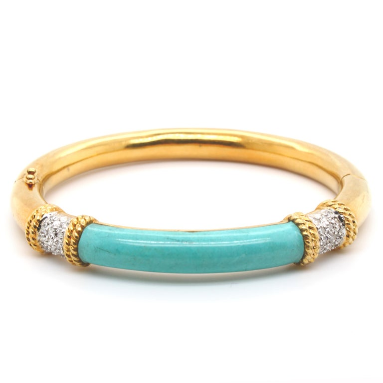 A lovely everyday gold bangle with an unusual curved turquoise top in yellow gold. It is bordered by gold wires and round brilliant cut diamonds. The bangle has a hinge and big opening as well as a security clasp for easy and secure wearing. The