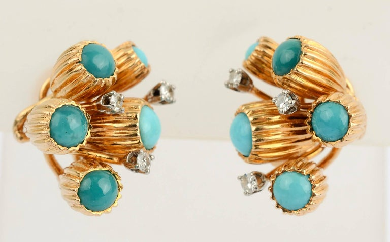 Unusual earrings with clusters of turquoise stones that are set in elongated, ribbed cups, perhaps meant to be bellflowers. In addition to five turquoise stones, each earring has three diamonds. Backs are clips and posts.
