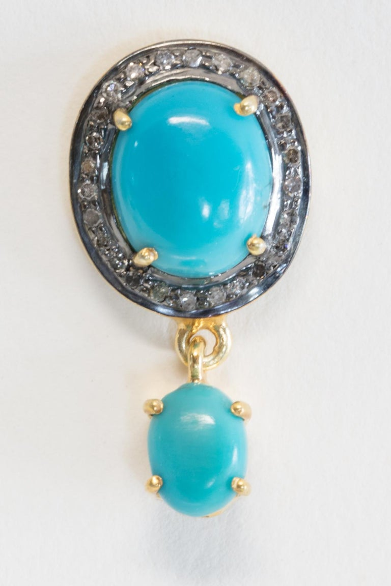 A pair of turquoise stud earrings bordered with pave` set diamonds with a smaller turquoise drop.  Post is 18K gold for pierced ears.  Sterling otherwise.
