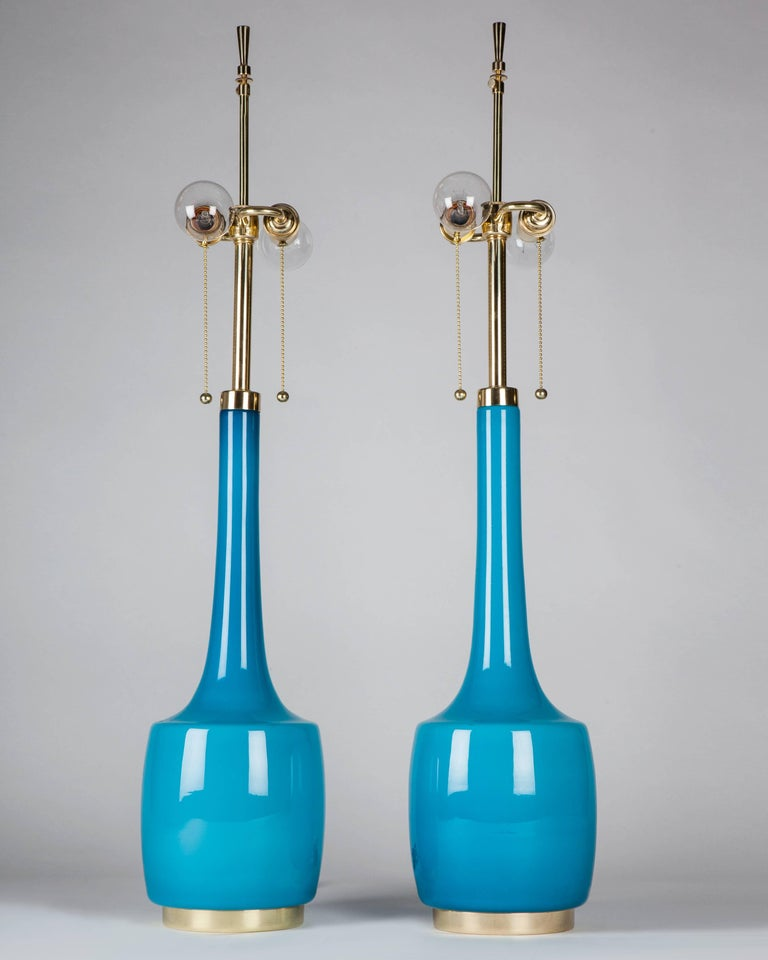 ATL1979 A pair of tall vintage cased glass table lamps in a vibrant turquoise blue having polished brass fittings. By the Swedish maker Bergboms. Due to the antique nature of this fixture, there may be some nicks or imperfections in the