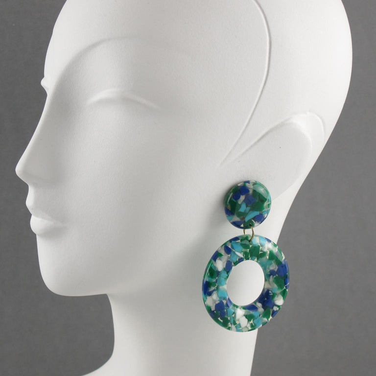 Beautiful bright colors oversized lucite clip-on earrings. Large donut dangling shape with a geometric design featuring clear lucite with colorful tiny chunk inclusions. Assorted colors of cobalt blue, emerald green, white and arctic blue. No
