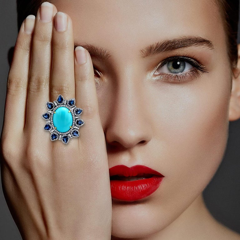This ring is crafted in 14-karat gold and sterling silver. It is hand set in 9.41 carats turquoise, 3.33 carats blue sapphire and .81 carats of diamonds.   FOLLOW  MEGHNA JEWELS storefront to view the latest collection & exclusive pieces.  Meghna
