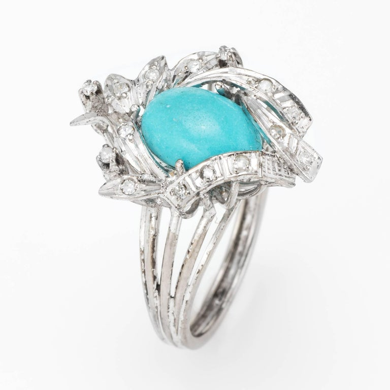 Elegant vintage cocktail ring (circa 1940s), crafted in palladium.   Centrally mounted cabochon cut turquoise measures 11mm x 8mm (estimated at 3 carats), accented with an estimated 0.15 carats of single cut diamonds (estimated at H-I color and
