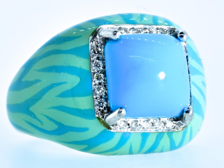 Turquoise, fine and natural and displaying a pleasing bright robin's egg blue color.  This prong set center stone is a high sugar-loaf cabochon.  20 fine white brilliant cut diamonds, all well cut and well matched, near colorless (G) and very very