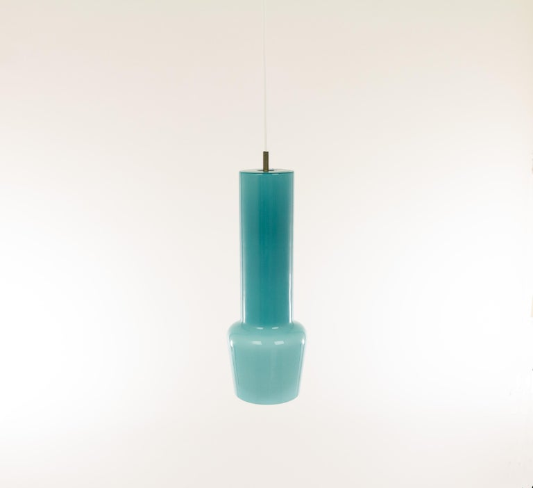 Hand blown turquoise glass pendant no. 011.11 designed by Massimo Vignelli at the start of his impressive career in design and executed by Murano glass specialist Venini. One of the most characteristic lamps that Vignelli designed for Venini.  The
