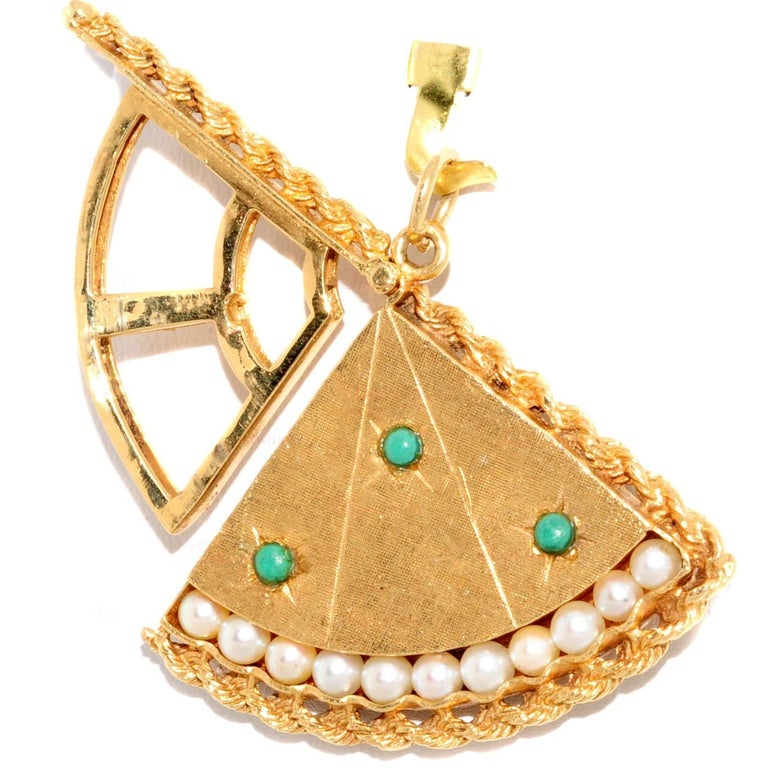 This unique locket in the shape of a fan was made in the 1950s - 1960s. It is crafted out of 18k yellow gold and is accented with 11 pearls and 3 turquoise stones. Measurements: 1.77