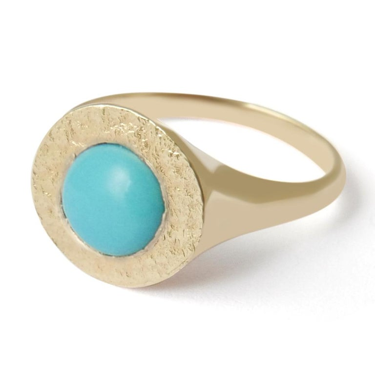 This textured signet ring crafted in solid 14-carat gold features a raised natural Arizona turquoise cabochon embedded in a shimmering texture.  The ring is finished with a high polish on the sides and band for a comfortable fit.  This ring is a UK