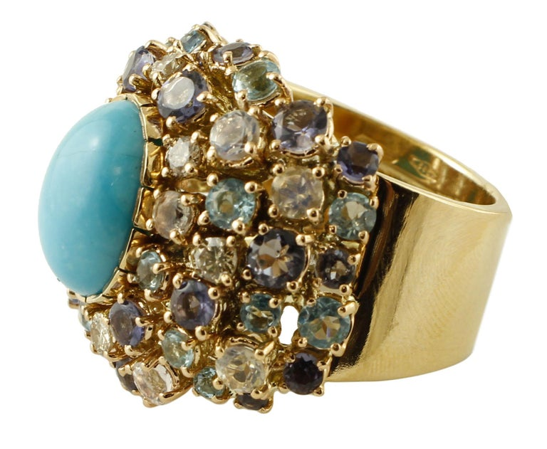 Beautiful vintage ring in 14 kt yellow gold structure, mounted with a central turquoise (1 x 1.3 cm) surrounded with diamonds, white sapphires, topazes and iolite. This ring is totally handmade by Italian master goldsmiths. Diamonds 0.44 ct White