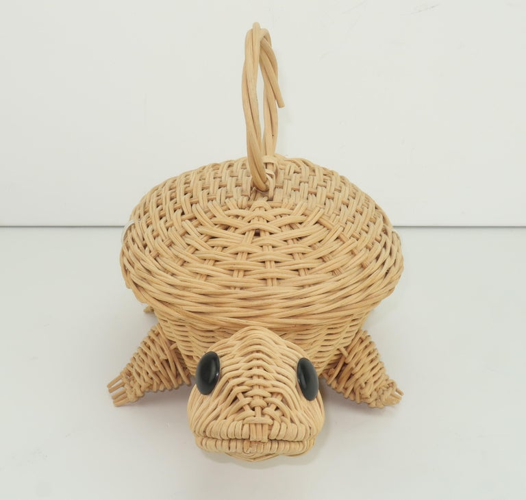 Adorable natural wicker basket handbag in the shape of a turtle on the move.  It has a ring shaped top handle with a black button and white elasticized cord closure which opens to a small but roomy interior.  He is the perfect accessory for a