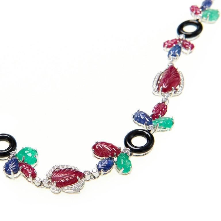 Ri Noor's Multi Gem Necklace is a striking statement piece that features an assorted collection of jewels including white diamonds, rubies, sapphires, emeralds, and onyx all set in 18k white gold. The colorful gemstones are carved and set in a