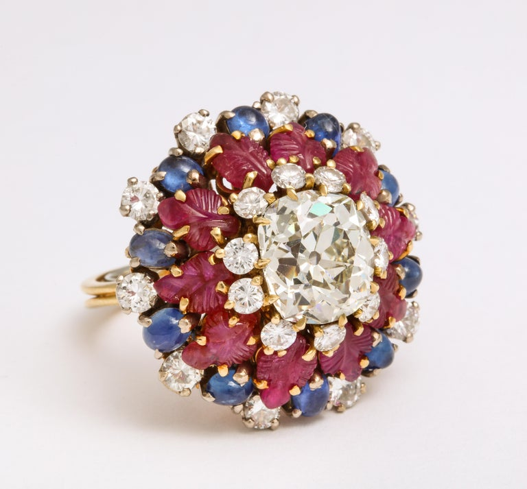A Tutti Frutti Ruby Sapphire Diamond Gold Cocktail Ring circa 1950, with old mine cushion cut diamonds, ruby leaves and oval cabochon sapphires in yellow gold, measuring an impressive 1 1/5 inches wide and 1 inch high.  Material: Yellow