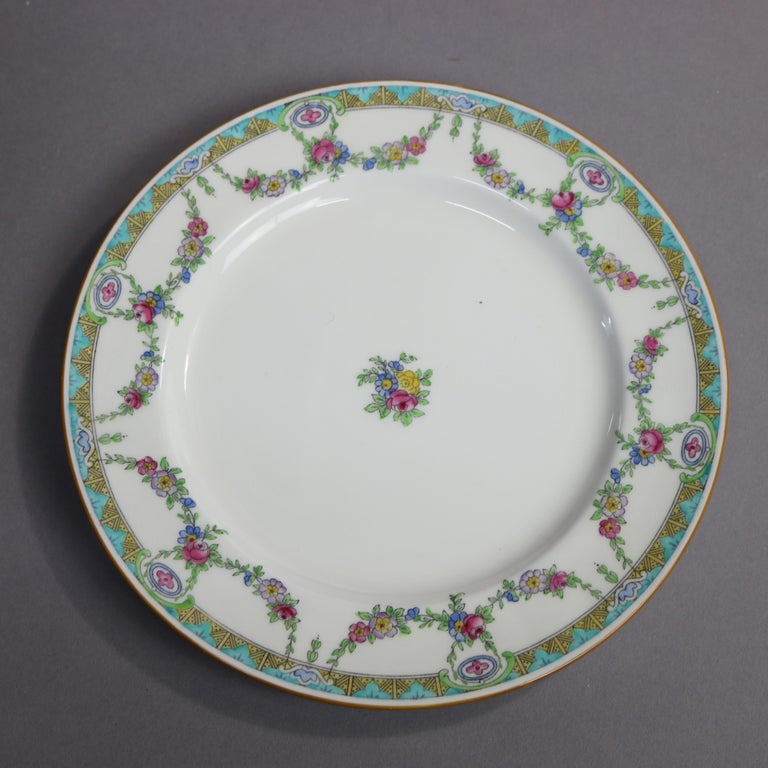 A set of 12 English Mintons Fine China salad plates feature rim with floral swag and stylized foliate border, central floral spray, en verso crown maker mark as photographed, 20th century  Measures- .75