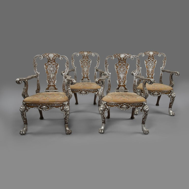 Twelve George I Style Carved Walnut and Silvered Dining Chairs by Lenygon & Morant.  This fine set of dining chairs comprises ten armchairs and two grand end chairs, or carvers, with arms.   Each chair has a shaped cresting rail above scrolled