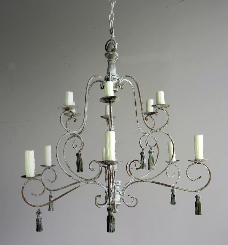 Twelve-light French iron and wood chandelier with beautiful worn painted finish. The fixture is newly rewired with drip wax candle covers. The chandelier includes chain and canopy. Twelve carved wood painted tassels throughout.
