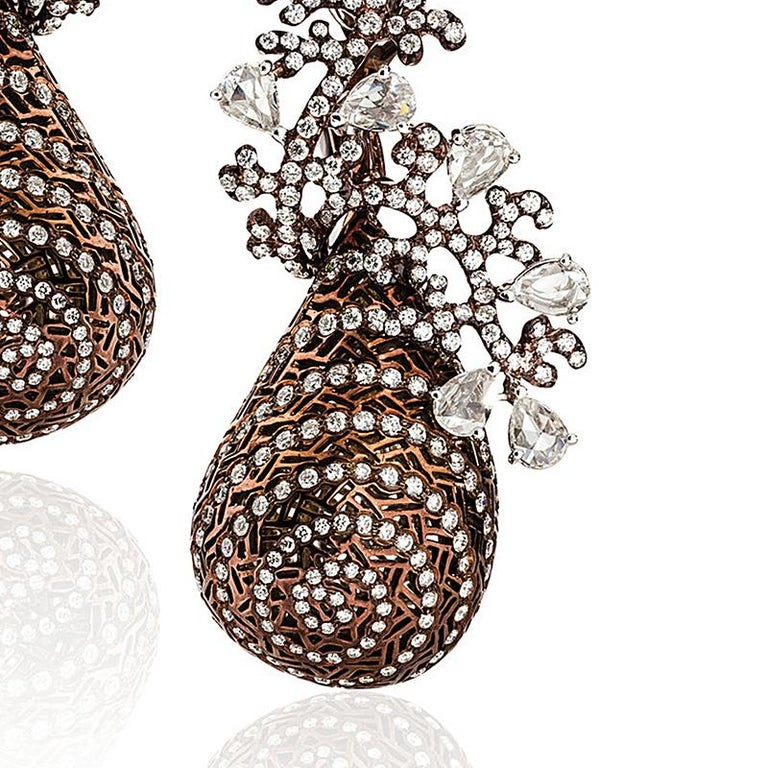 A pair of modern Twirling Shimmer earrings by Neha Dani. These earrings are 18 karat white gold and bronze rhodium and have a full tear-shape drop enlivened with radiating spiral patterning, striations of diamonds, textured bronze rhodium-plated