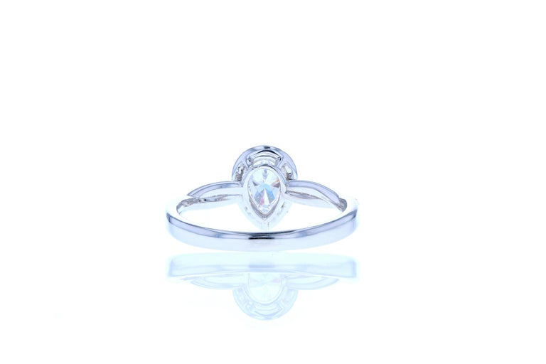 A dainty and elegant pear shaped diamond engagement ring featuring pear shaped center diamond surrounded by a delicate diamond halo to increase the perceived size of the center stone. The shank is an elegantly undulating band with one row of diamond