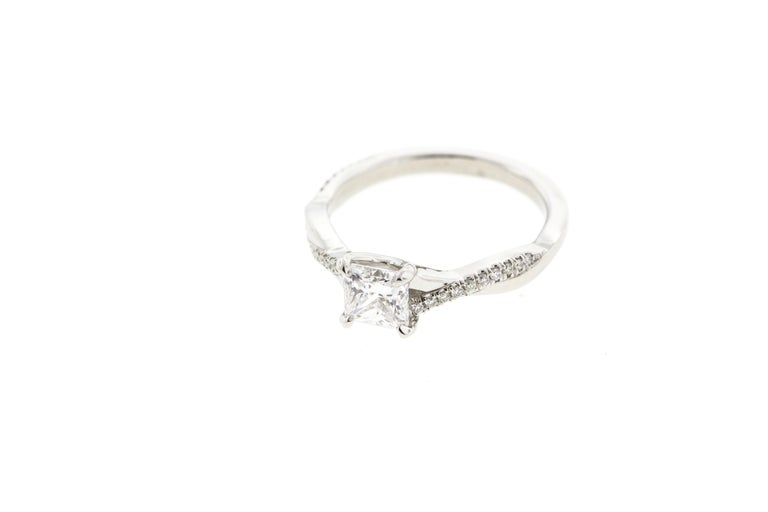One of our most popular ring designs, with a princess center diamond! This Twisted White Gold Diamond Engagement Ring is crafted in 18KT White Gold and contains a Princess shape Diamond (1.00 total carat weight) with surrounding diamond pave to