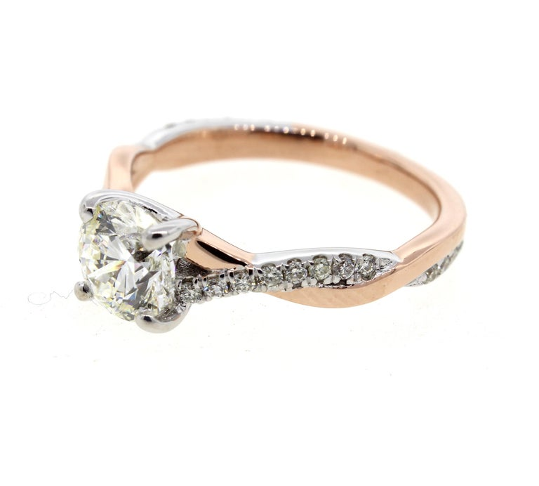 This two tone white and rose gold diamond engagement ring has a twisted rope design and features diamond pave on the band. Combining the best of both worlds, this sweet engagement ring is a perfect combination of all the elements. This ring is