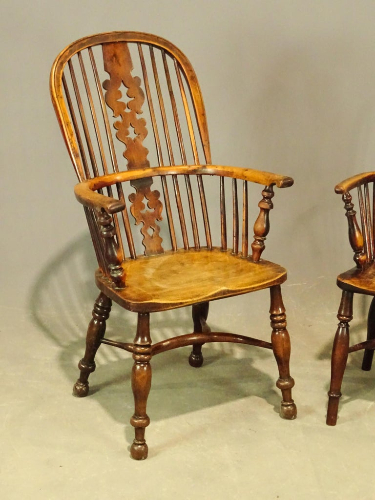 Two complementary antique English Windsor dining armchairs with wonderful aged wood patina. Chairs are hand carved with crinoline stretcher, body of the chair is beautifully figured yew, the seat is a single slab. Sold individually. Chair on left
