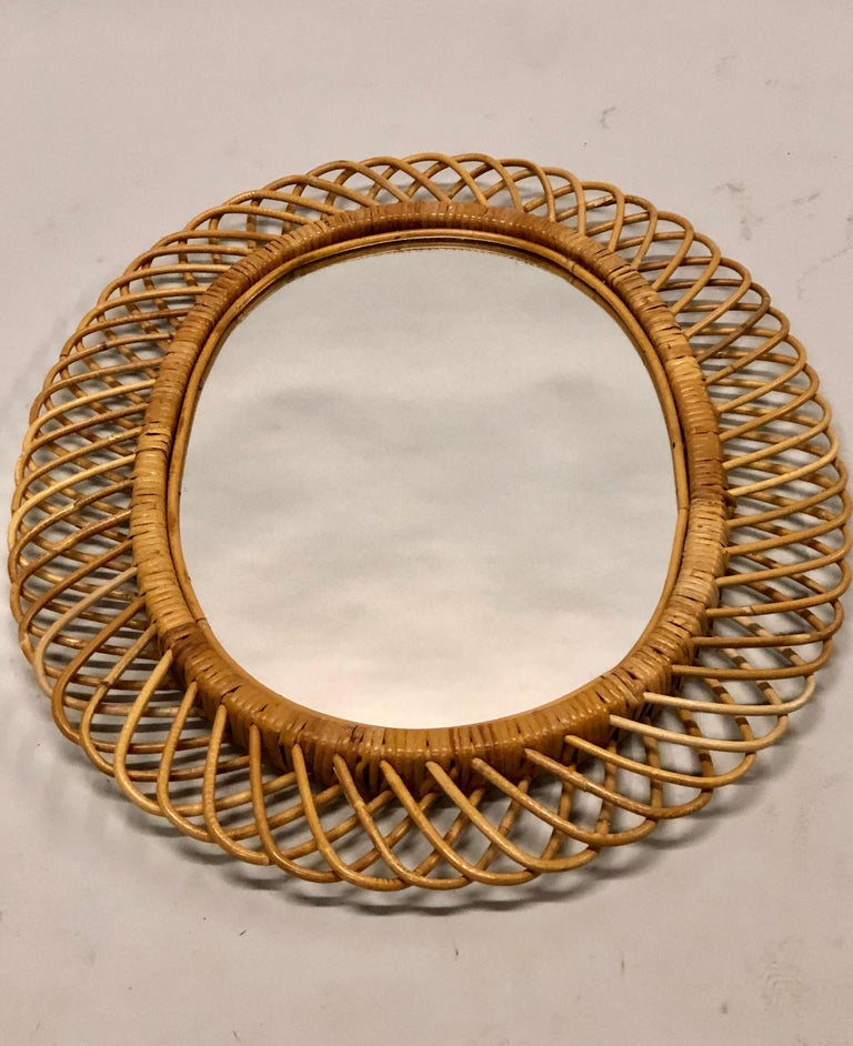 Two (2) Italian Mid-Century Modern rattan and bamboo wall mirrors attributed to Franco Albini. Each mirror is shaped in the form a sunburst.
