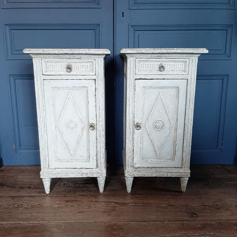 Set of two antique Directoir cabinets or nightstands from the 19th century. These stunning French cupboards or bedside tables made of oak / beechwood are finished in a beautiful aged gray patina with a marble look top.  Measurements: H 81 x W 43 x