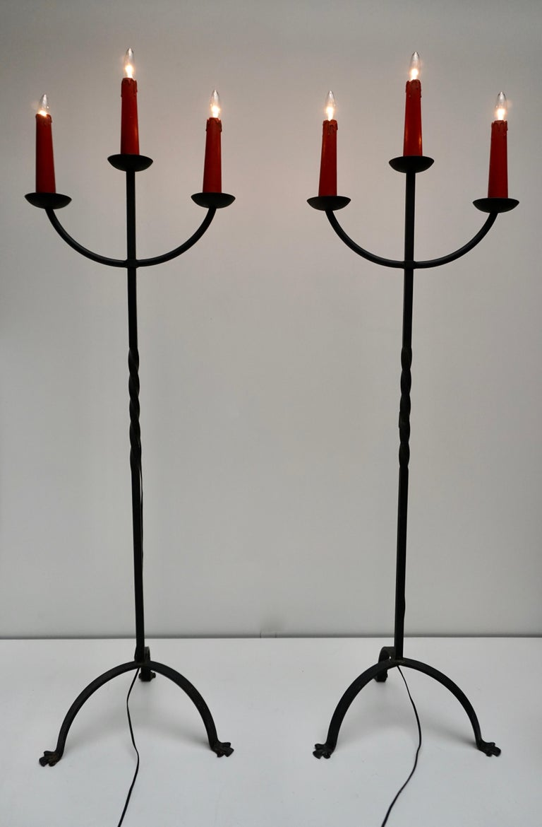 Direct from France. Two gorgeous 3-light antique wrought iron floor lamp with candle holders, like an antique candelabra fresh out of a French country home or chapel! Three deep metal cups each hold a faux wax candlestick over the wired sockets.