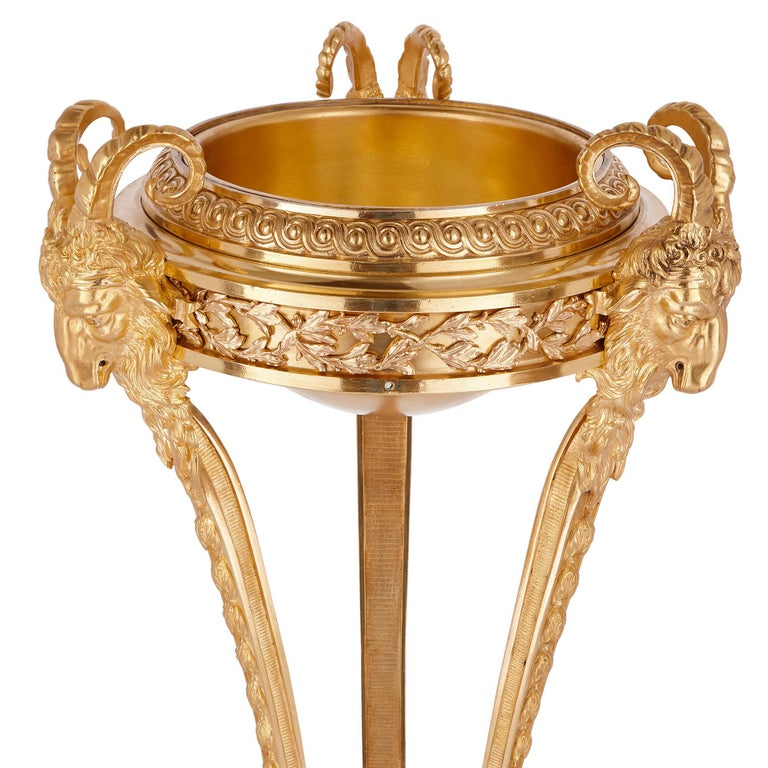 These large, gilt bronze tripod stands have been designed in a majestic French Neoclassical style.   Both stands serve to support bowls, raising them high off the ground. The bowls are held in place by gilt bronze friezes, ornamented with entwined