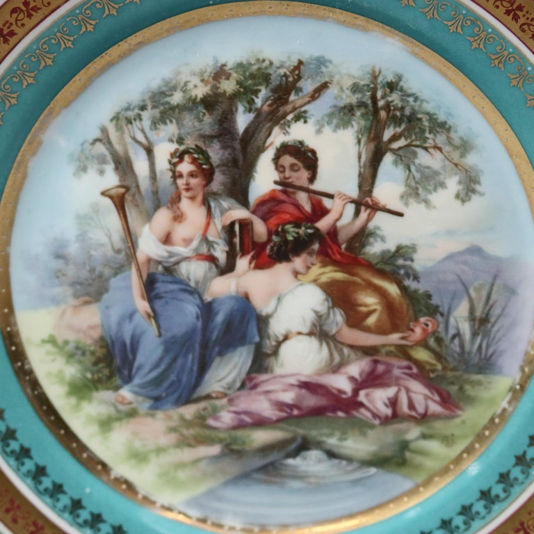 Two antique and hand painted Porcelain plates by Royal Vienna offer central and scene is classical muses in countryside setting, gilt highlights throughout, en verso beehive shield maker mark as photographed, 19th century.  ***DELIVERY NOTICE – Due