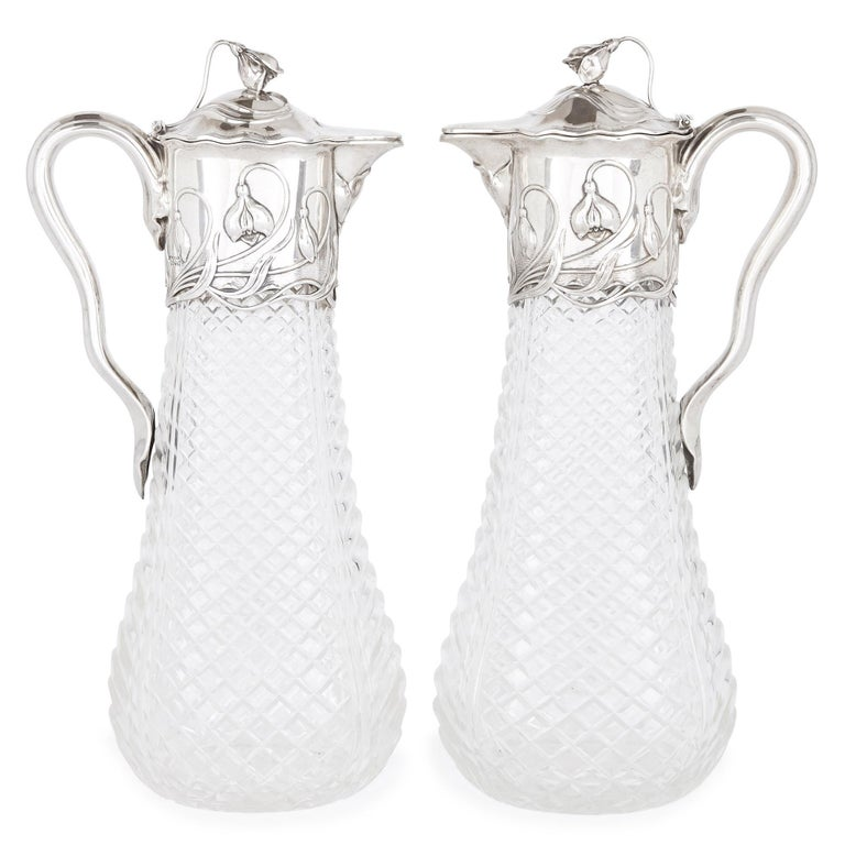 These graceful cut glass and silver claret jugs are designed in the Art Nouveau style. This style flourished in the arts in Europe in the late 19th-early 20th century. It was characterised by its use of continuous, serpentine lines and motifs, which