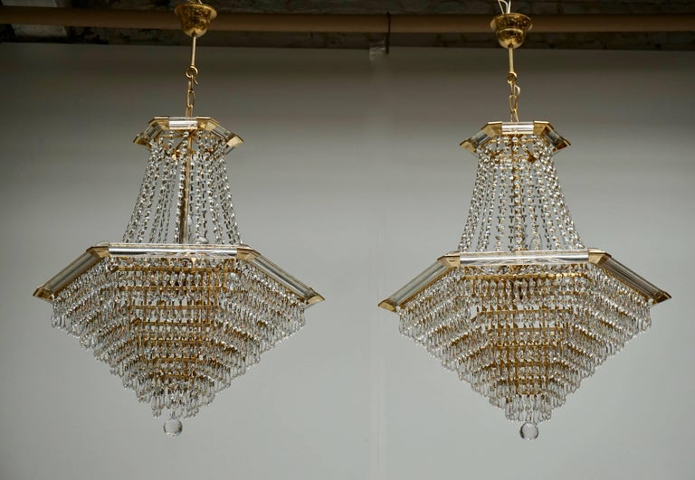A set of two (a pair of) very exclusive and high quality chandeliers by Bakalowits & Söhne, Austria, manufactured in midcentury, circa 1960. They are made of a gold-plated brass frame decorated with hundreds of faceted glass crystals. Measures: