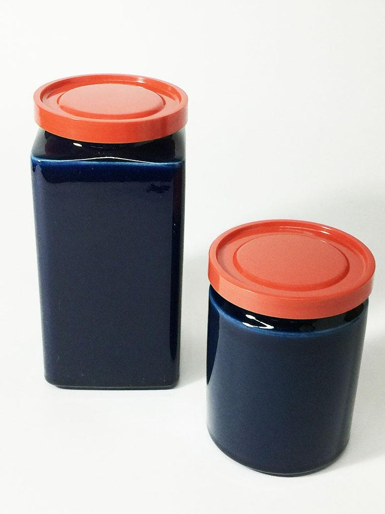 Two blue and red Arabia Finland stock jars, 1949-1954  The lidded jars are stackable, by placing the round on the square The porcelain jars has a lid made of strong solid plastic Marked on the bottom, used during 1949-1954  The measurements