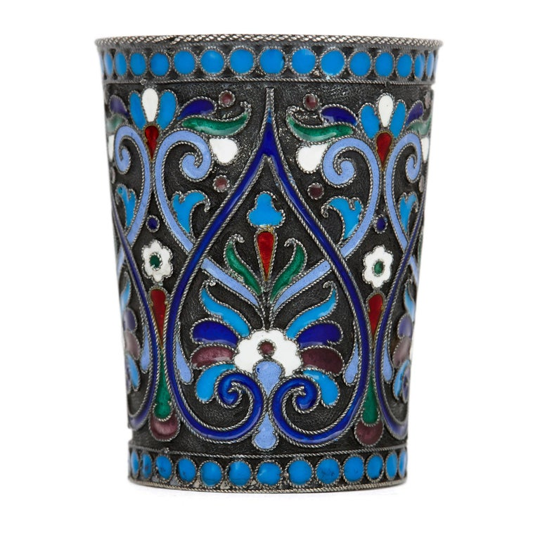This matching pair of early 20th century Russian drinking cups (or vodka cups, also known as beakers) are made of solid silver. Cylindrical in form, the cups narrow slightly from the rim to the base. The cloisonné enamelwork of each cup is extensive