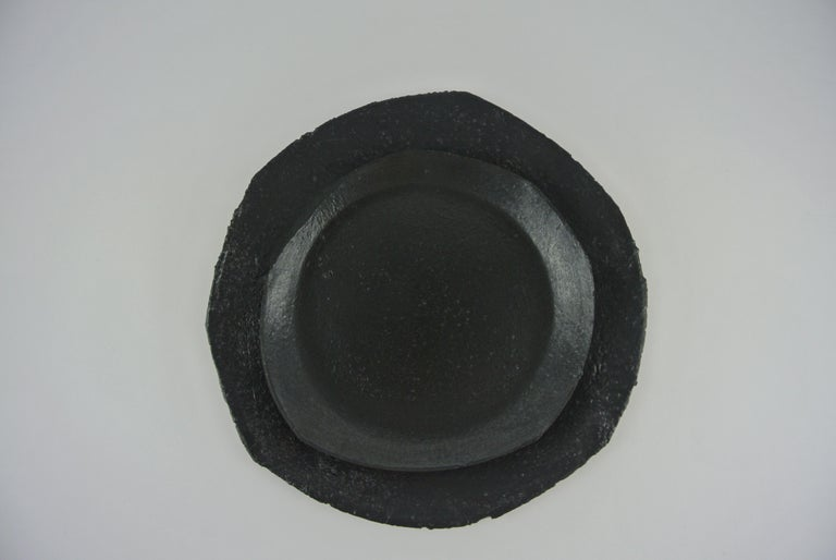 Set of one dinner plate and one lunch plate in stoneware. Black silvery glazes. Each plate is rolled, shaped and cut by hand resulting in a variety in thickness and shape. Material: white, red and brown stoneware with different degrees of fire sand