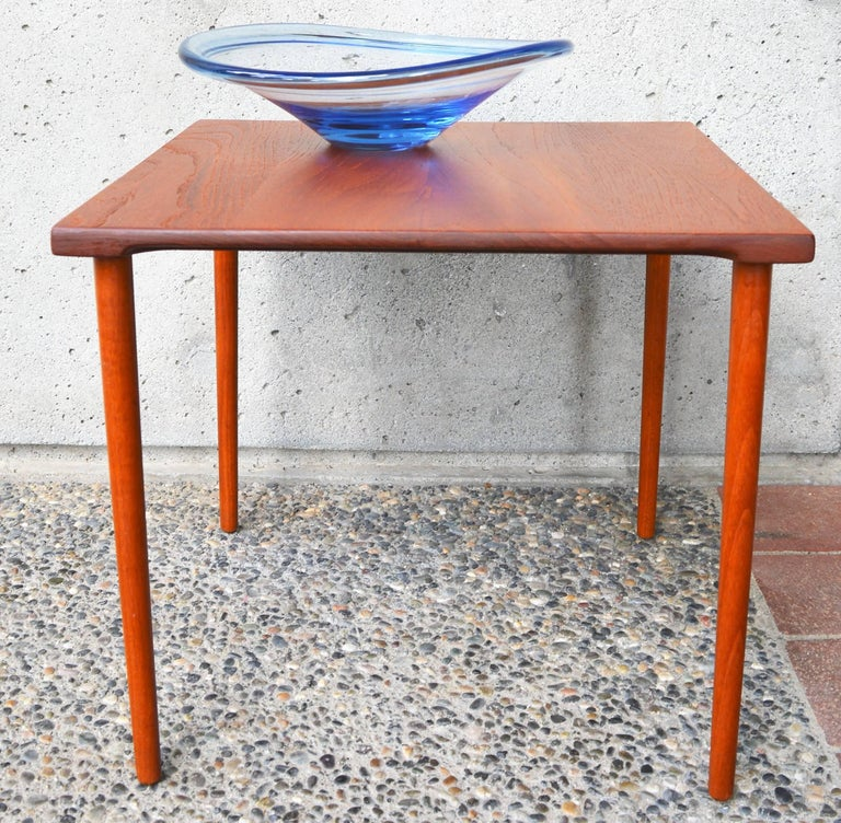 These lovely and minimalist Danish modern teak side tables were designed by Peter Hvidt & Orla Mølgaard-Nielsen in the 1960s for France & Daverkosen / France & Son. Made entirely of solid teak, the top has gorgeous grain, and each side has an arced