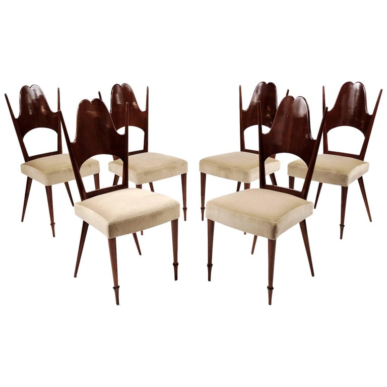 Tinted fruitwood. Splat-back dining chairs, all raised on round and tapered legs, terminating in carved foliate feet.
