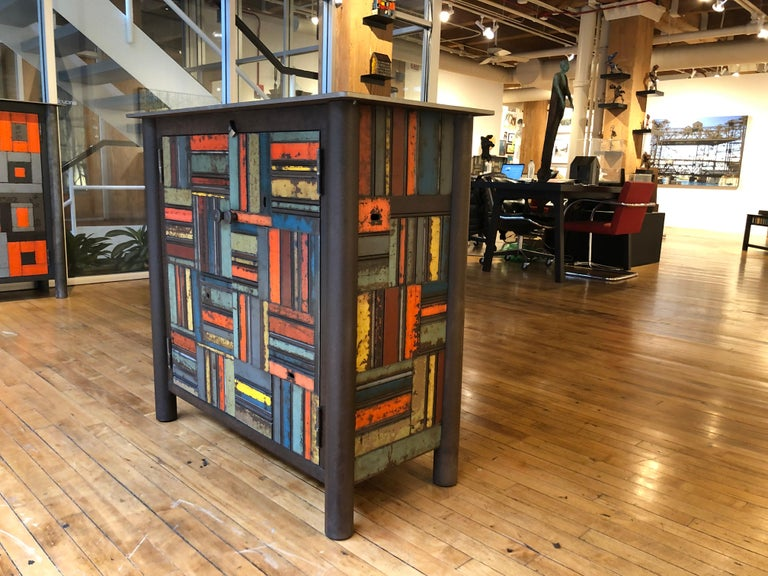 This is a totally functional two door cupboard. It is created from natural rusted steel and found steel. The legs are made from salvaged pipe. The panels on the door fronts and sides are made from salvaged pieces of steel with the original paint and