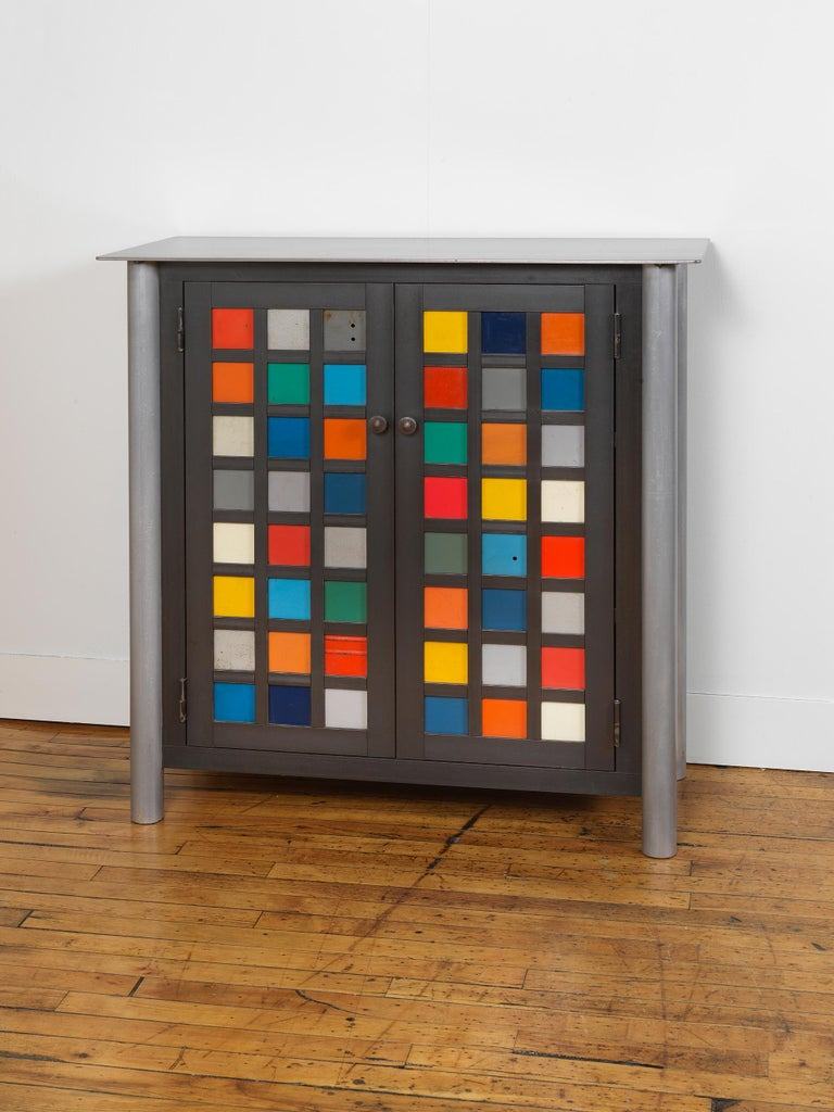 This totally functional cabinet with two interior shelves is created from hot-rolled steel and found painted panels. The panels on the door fronts and sides are created from blocks of painted salvaged and recycled steel. This unique custom piece is