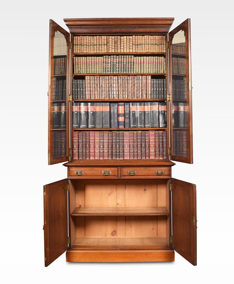 Walnut bookcase having flared moulded cornice over two beveled glazed doors enclosing four adjustable shelves. The protruding base having two short draws with brass handles. Above two paneled doors opening to reveal single shelf, all raised up on