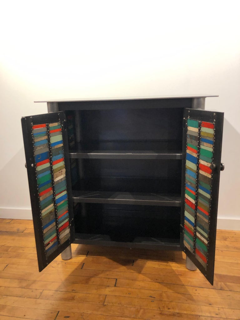 This is a totally functional two door cupboard. It is created from hot-rolled steel and found steel. The legs are made from salvaged pipe. The panels on the door fronts and sides are made from salvaged pieces of steel with the original paint and
