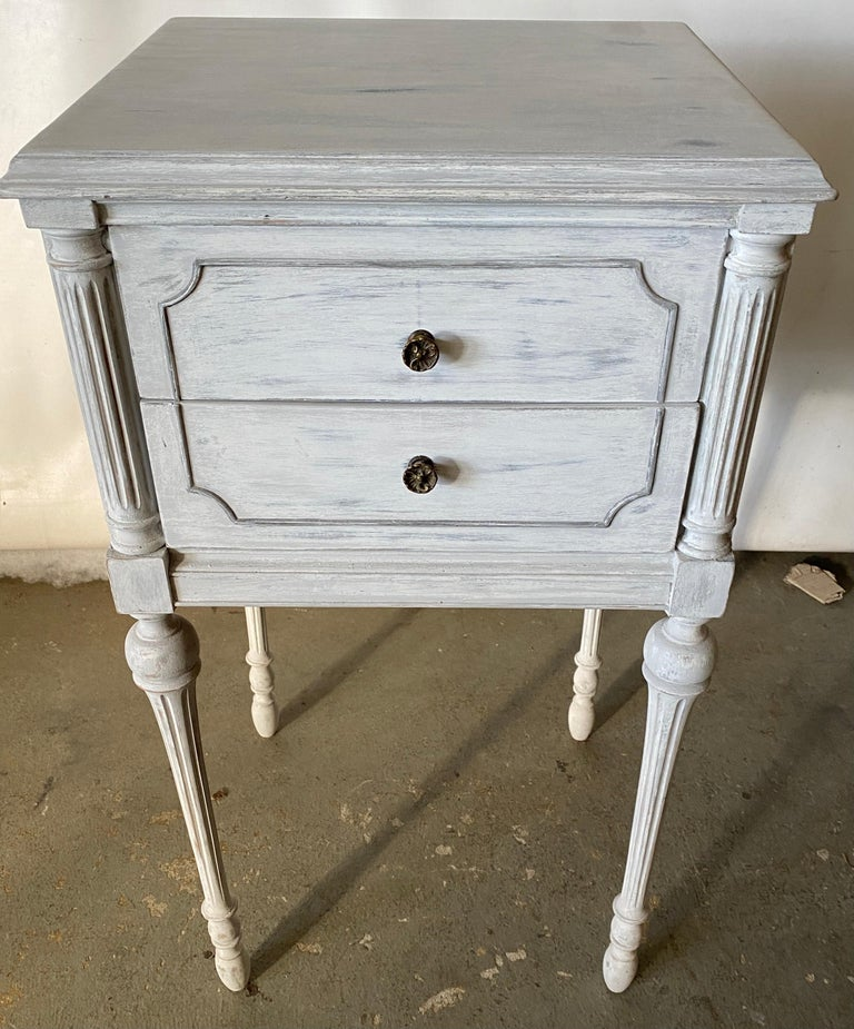 The grey and gold gilt painted metal night stand has an open upper shelf with a pull out tray with a cubby hole or lower shelf for more storage. This night table or stand will fill the bill if you are searching for a Swedish Gustavian, neoclassical