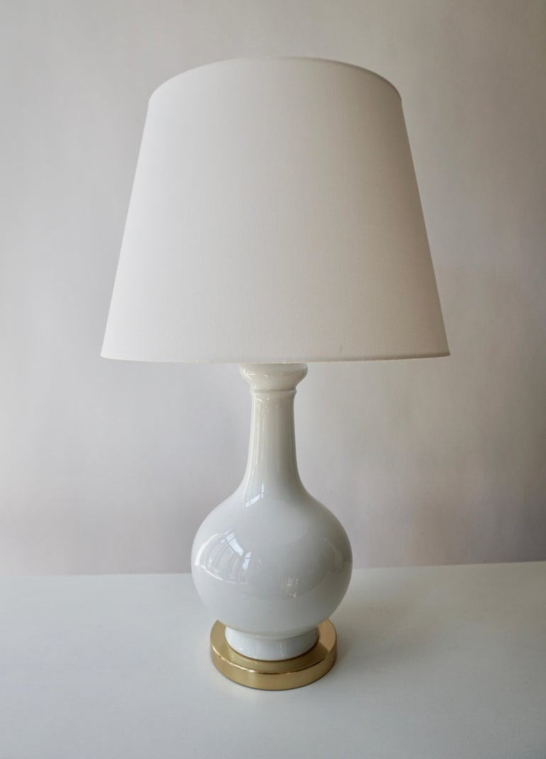 Two elegant white porcelain Italian Mid-Century Modern table lamps on a brass base. Measures: Diameter 16 cm. Height 36 cm.  The lampshades are not included in the price.