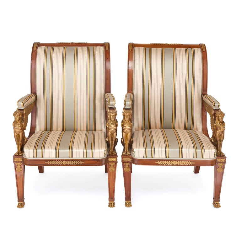 These majestic armchairs are prime examples of Empire style furniture, featuring Egyptian Revival sphinx-themed armrests and further classically-inspired detailing. Crafted from mahogany, the chairs have been decorated with gilt bronze mounts and