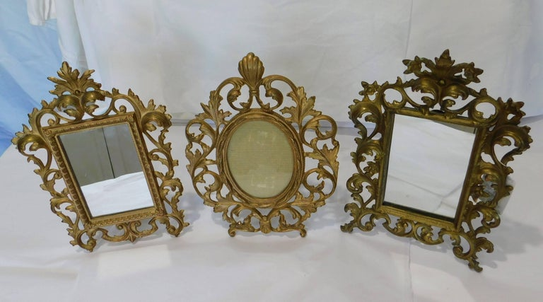 These two English gilt bronzed table vanity mirrors are in very good condition and are in the Rococo style. Measure: Two rectangle mirrors measure 8 x 11.25 x 1.25 inches and 8 x 11.50 x 3.25 inches. The oval frame is 8.5 x 11 x 4 inches and can be