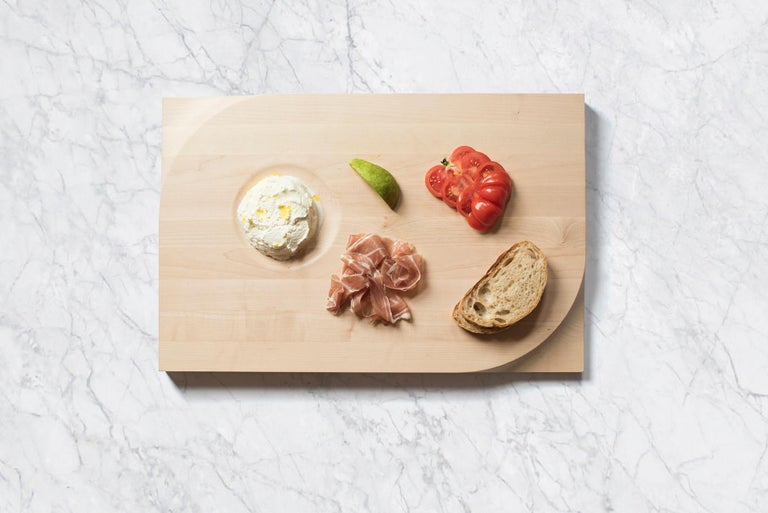 Beauty meets function. The two-sided cutting board is made with European maple butcher block and carved at the corners with an ergonomic shape for easy handling. It's a dinner party staple accommodating your laborious food preparation on the broad,
